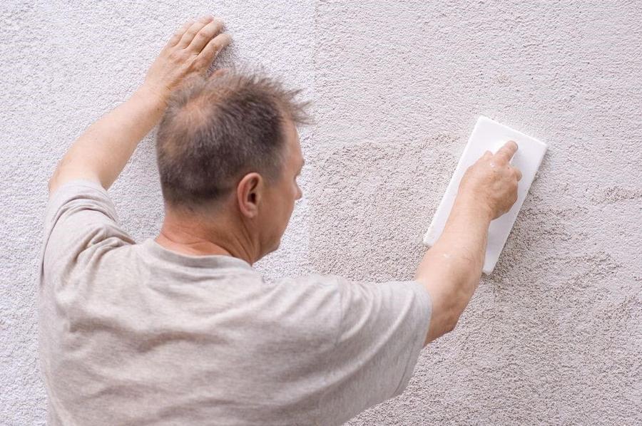 мужчина наносит минеральную штукатурку вручную