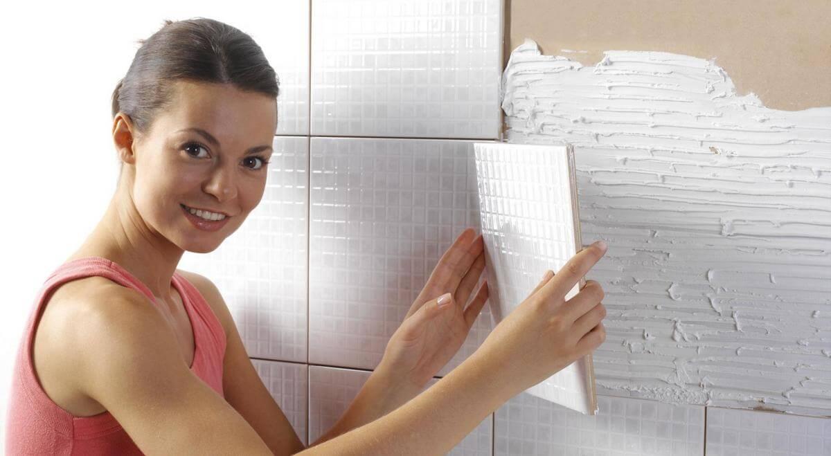 девушка укладывает плитку на стену